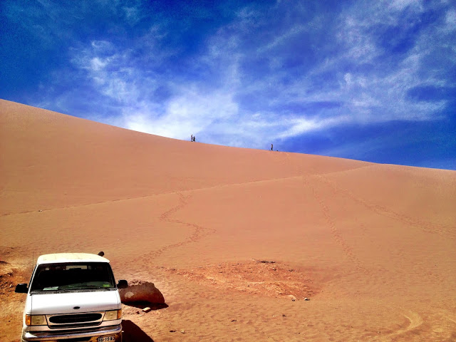 Climbing a sand dune to go sandboarding - Valley Of The Moon, Atacama Desert, Chile