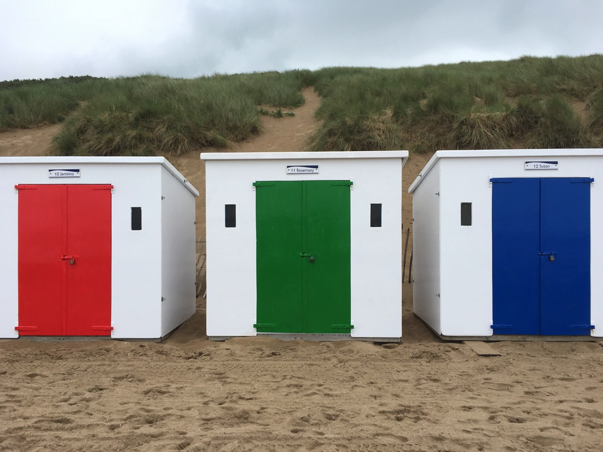 Colourful beach huts at the entrance to Woolacombe beach, Devon