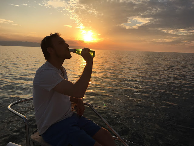 Simon Heyes drinking a beer and watching the sunset over Lake Malawi